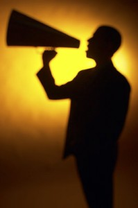A man with a megaphone, announcing something far and wide.