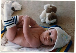 Photo of a boy baby straight from his bath, lying on his back in a bathtowel, wearing tube socks.